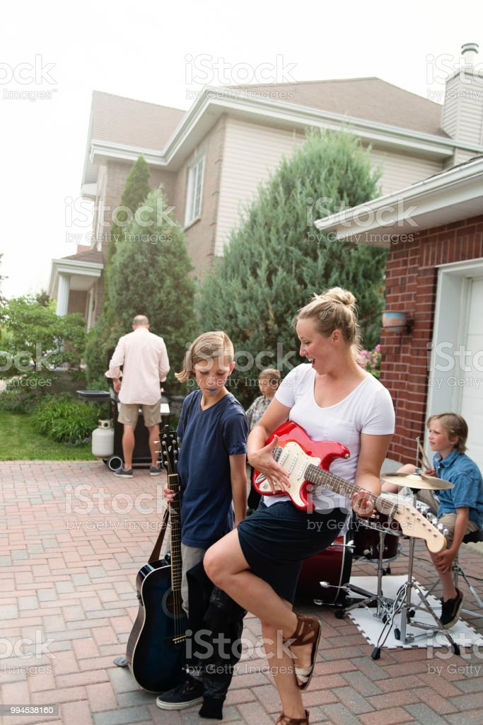 Mom pretending to be a rock star in family driveway. stock photo