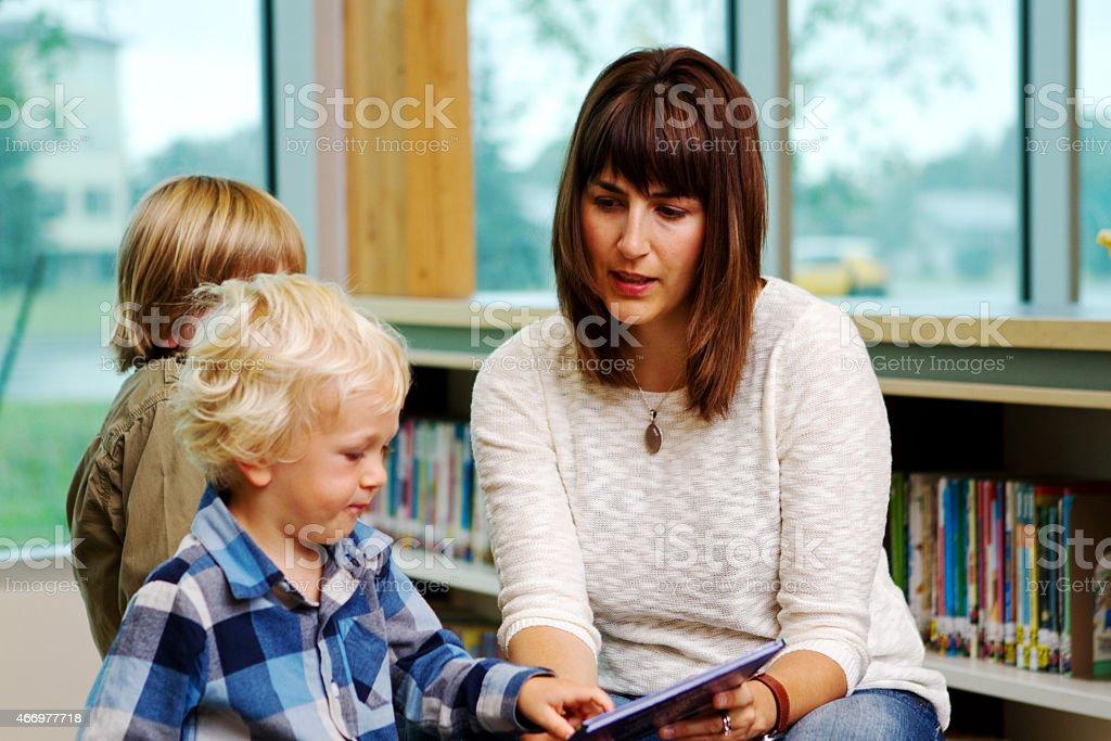 Mom reading book to children stock photo