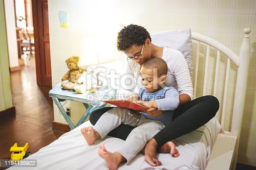 Mom and son in the bedroom reading book