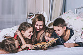 istock Mom reads a book to their children in bed 614131070