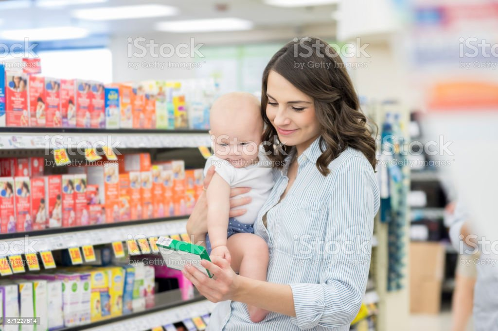 Mom reads label on over the counter medication stock photo