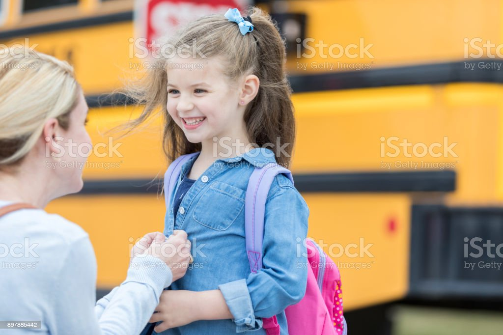 Mom sends her daughter off to school stock photo