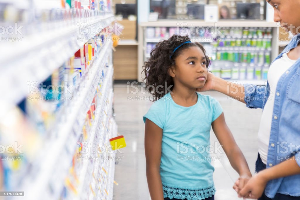 3047b6ad825 Mom shops in pharmacy for medication for sick daughter royalty-free stock  photo