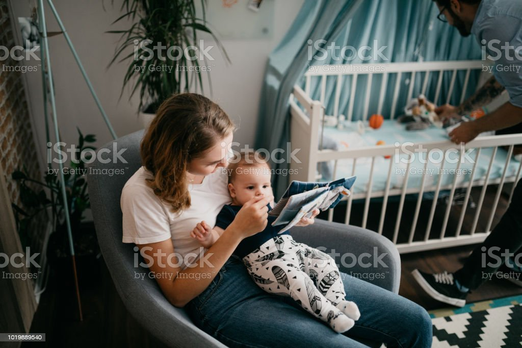 Super Mom Sitting In A Rocking Chair And Holding Her Baby Stock Pdpeps Interior Chair Design Pdpepsorg