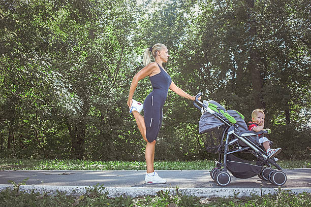 Mom stretching while holding stroller. stock photo