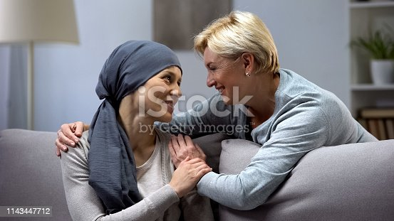 Mom supporting and hugging her daughter with cancer, visits in oncohospital
