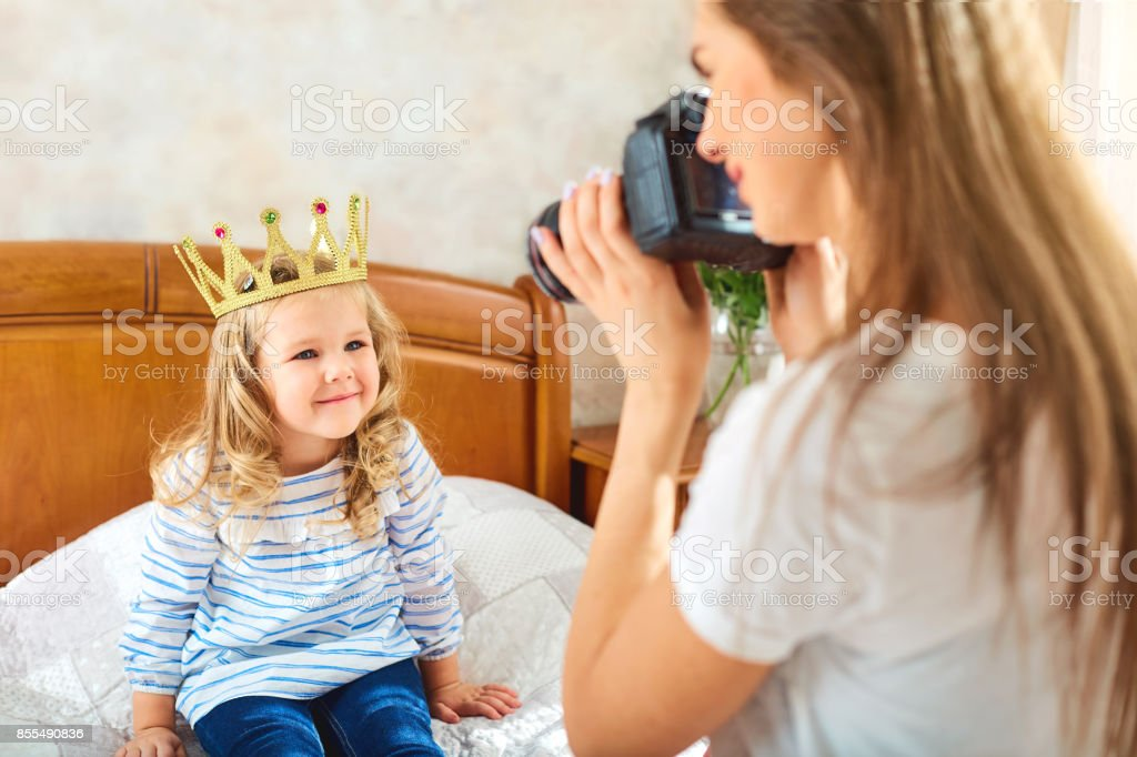 Mom takes pictures of her child in a room by the window. stock photo