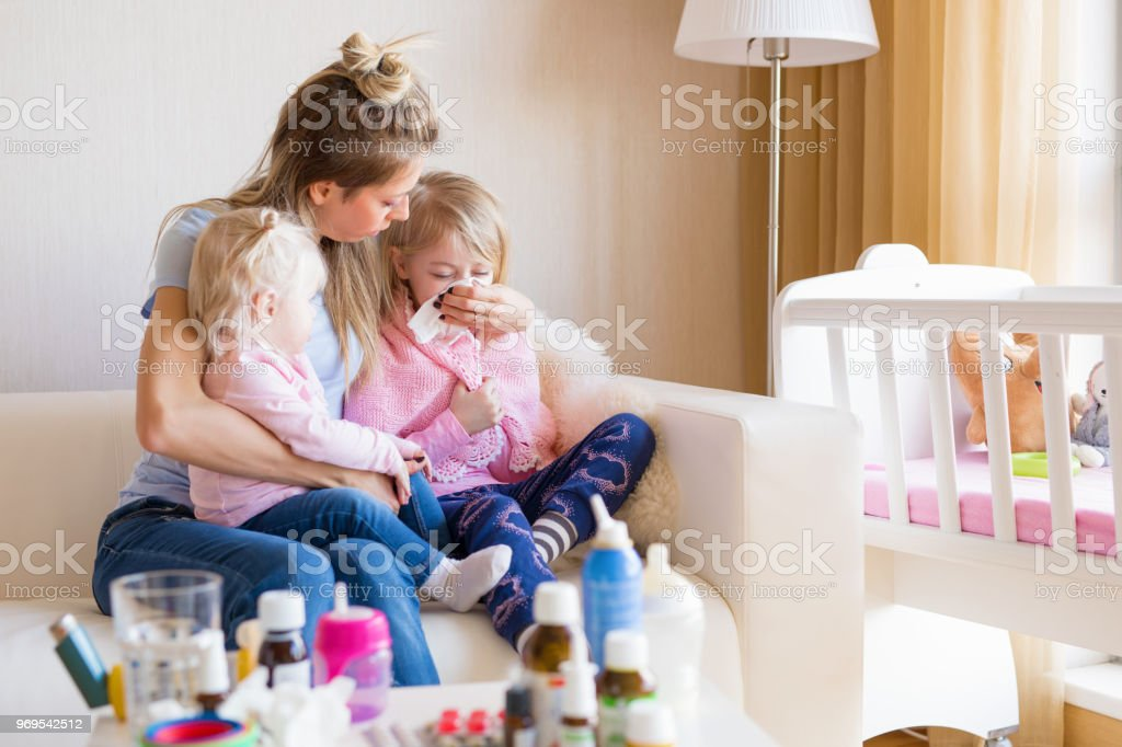 Mom taking care of her sick children. stock photo