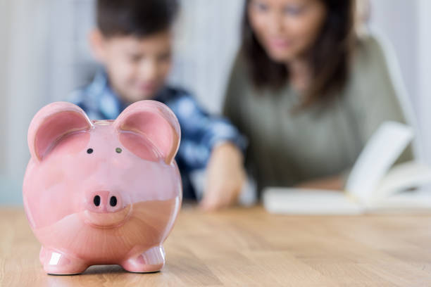 Mom talks about saving for the future with her son A pink piggy bank sits on a table. A mom and son are in the background. She is  teaching her son about saving his money. allowance stock pictures, royalty-free photos & images