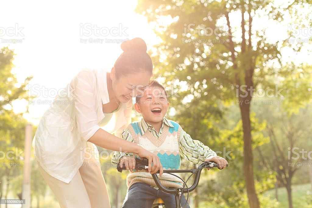 Mom taught his son in the park riding a bike stock photo