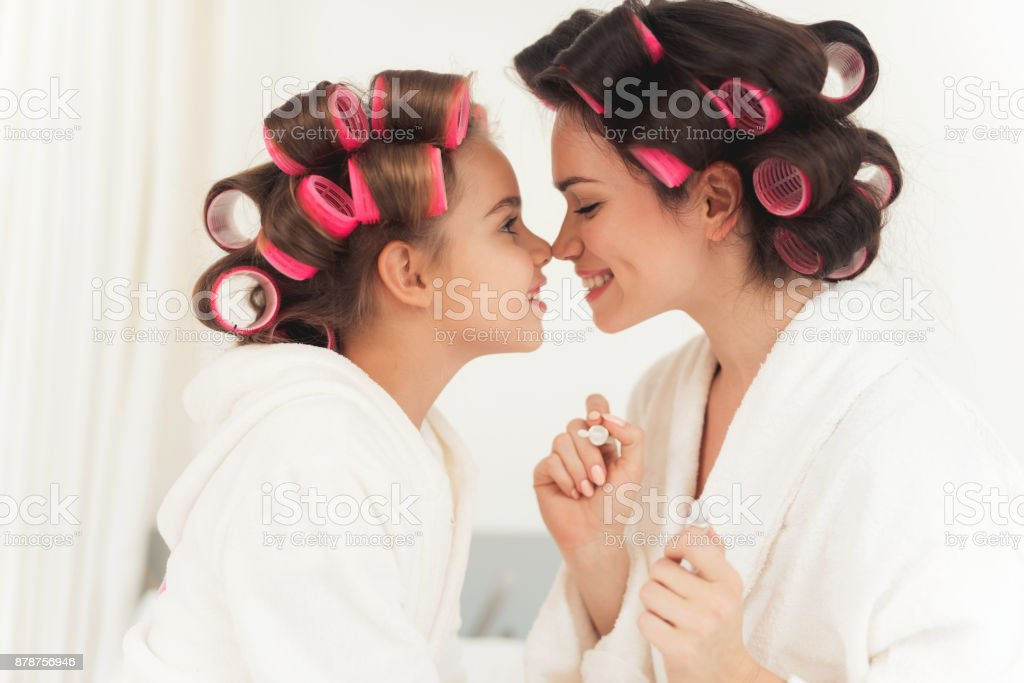Mom teaches a little daughter to do makeup. stock photo