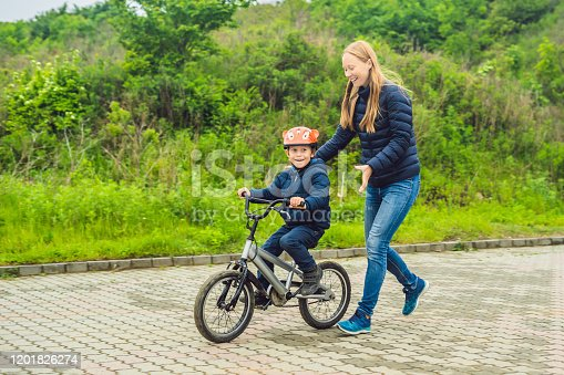 665192886 istock photo Mom teaches son to ride a bike in the park 1201826274