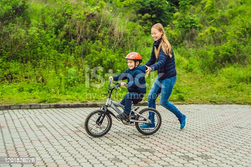 665192886 istock photo Mom teaches son to ride a bike in the park 1201826276
