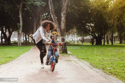Cute boy learning to ride a bicycle with his mother. Woman teaching son to ride bicycle at park.