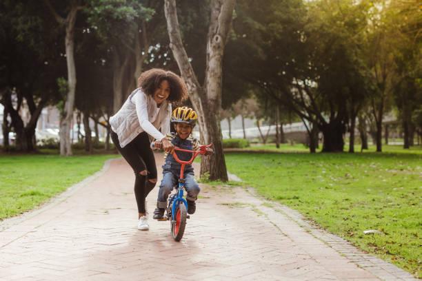 mamma insegna a suo figlio in bicicletta al parco - ciclismo foto e immagini stock