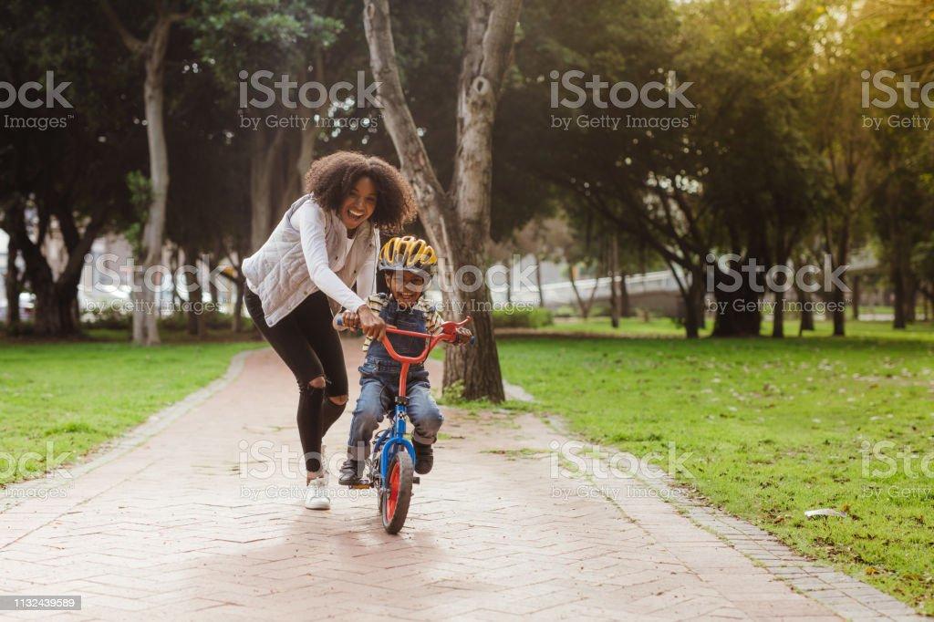 Mom teaching her son biking at park stock photo