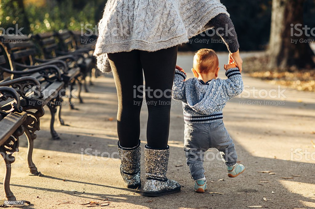 Mom teaching her son's first baby steps in the park stock photo