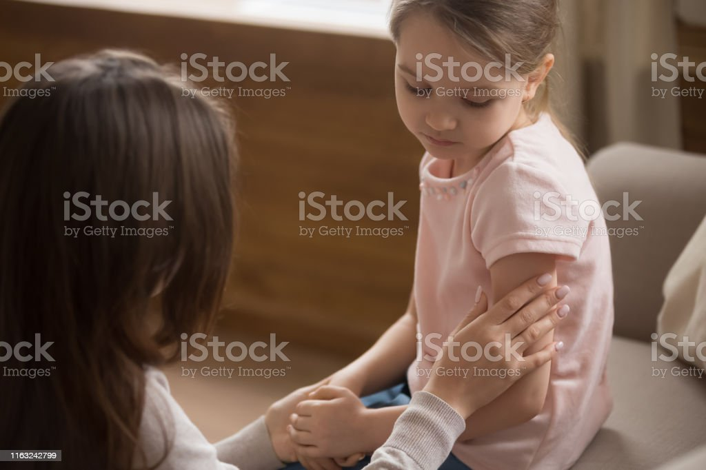 Mom touch caress unhappy preschooler daughter sitting on couch - Royalty-free Adoption Stock Photo