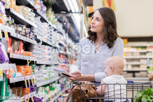 istock Mom uses grocery list while shopping in supermarket 871227808