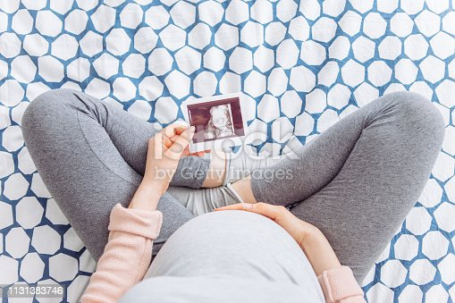 9 months pregnant young woman holding hand on her belly, she is sitting on bed and hold ultrasound image of baby