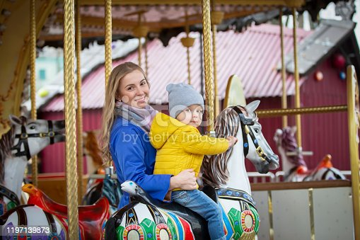 Mom with a cheerful baby on a carousel.Little son with mom in the park.
