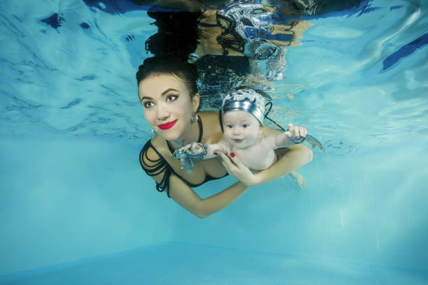Mom with a little son smiling dives underwater in a swimming pool stock photo