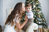 Happy family mother and little son near christmas tree on Christmas Eve at home. A woman and a little boy are resting in the white bedroom near the Christmas tree. Family at home. A young mother plays with her son waiting for the New Year