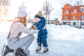 Mom with baby boy 3-5 years old, learn to train, ride in winter city on rink, ice skating. Happy smiling children play having fun weekend weekend first steps child ice skating. Free space for text
