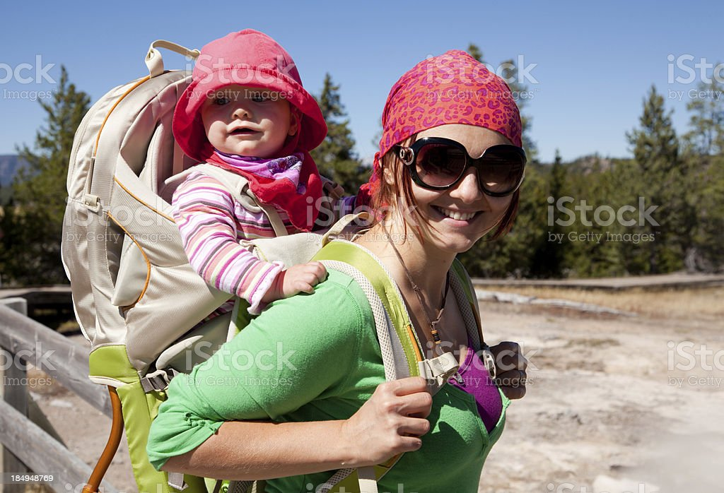 Mom with baby daughter in backpack carrier royalty-free stock photo