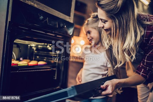 istock Mom with daughter cooking. 884618764