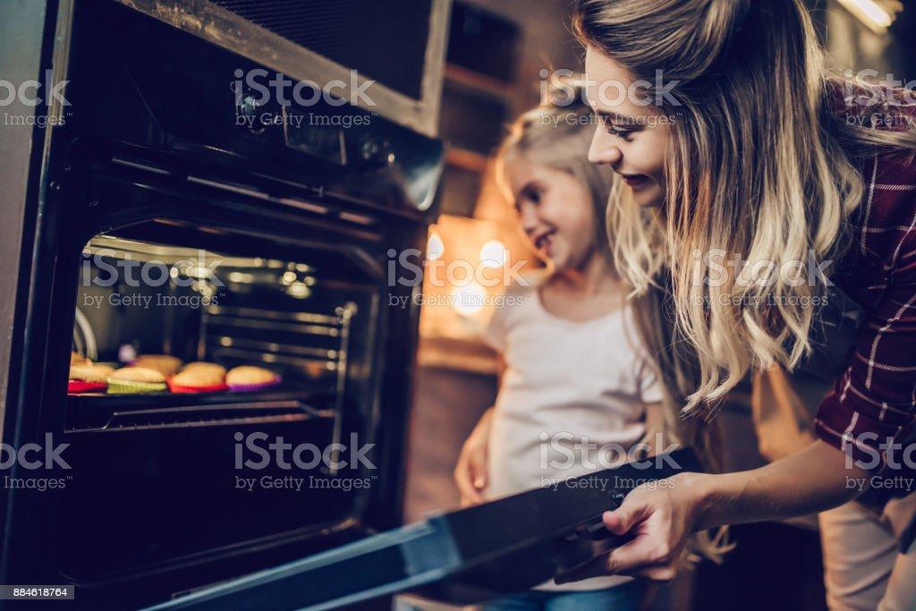 Mãe com a filha a cozinhar. - foto de acervo