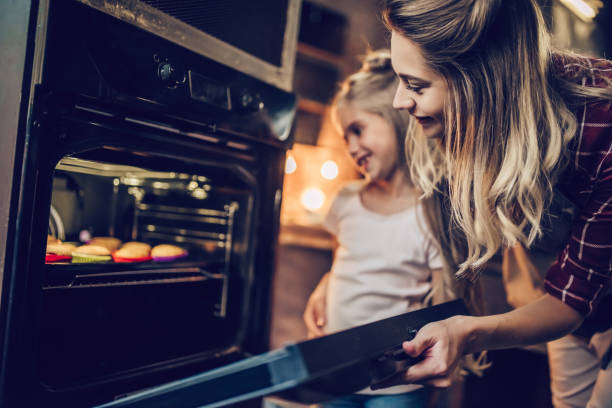Mom with daughter cooking. Attractive young woman with her little cute daughter are cooking cakes on kitchen. oven stock pictures, royalty-free photos & images