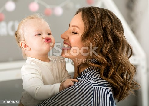 istock Mom with daughter on her arms emotionally hugs her at home 921879764