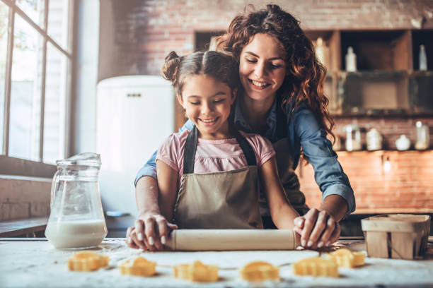 mom with daughter on kitchen. - kids cooking stock photos and pictures