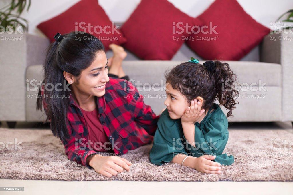Mutter mit Tochter auf Teppich zu Hause entspannen – Foto