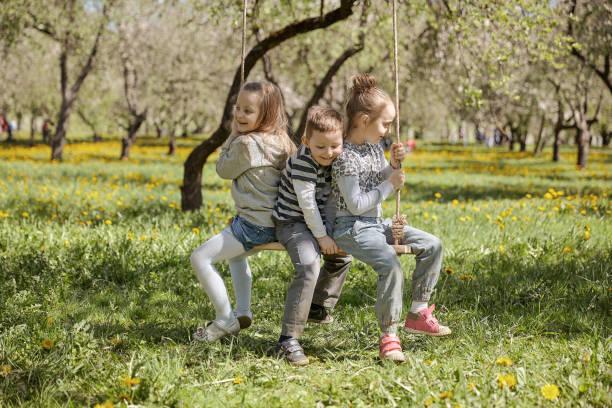 Mama mit ihren drei Kindern ruht im Sommerpark – Foto