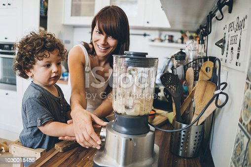 Mom with her toddler boy prepares healthy food together using blender