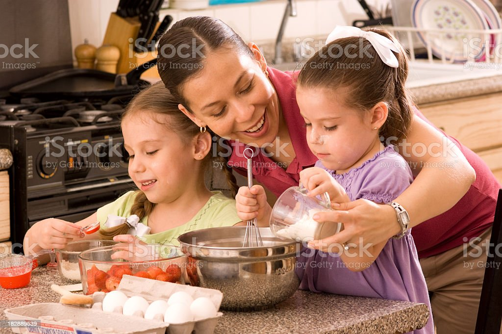 Mom with her two daughters baking in the kitchen royalty-free stock photo