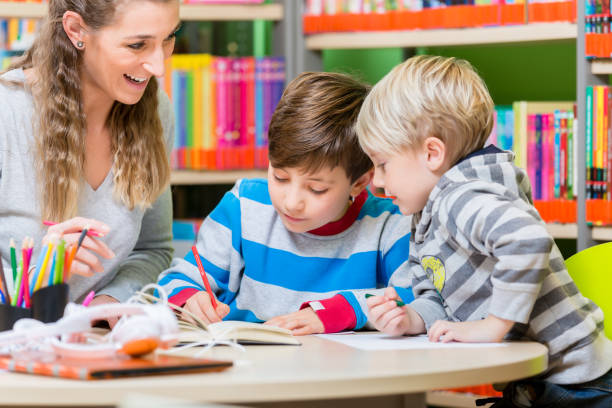 Mom with her two sons spending time in the library Mom with her two sons spending time in the library reading books community center stock pictures, royalty-free photos & images