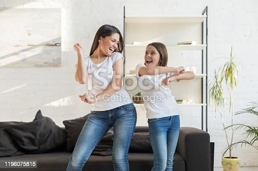 Mom with kid girl dancing in living room