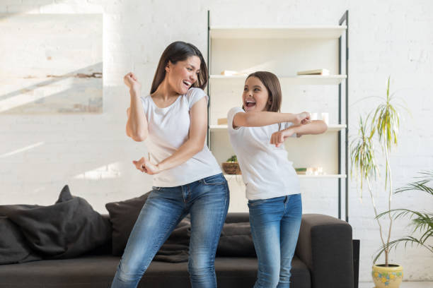 Mom with kid girl dancing in living room stock photo