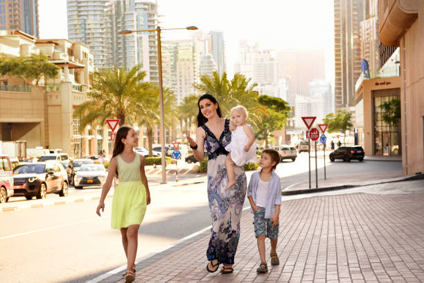 Maman avec des gosses marchant autour de la ville. - Photo