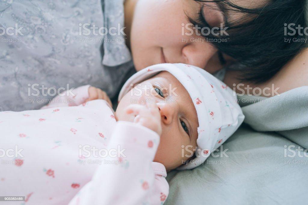 Mamá con gusto oler a su bebé recién nacido - foto de stock