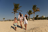 Mom with three kids walking on the beach. Woman with three kids in white shirts walking along the shore of the sea.