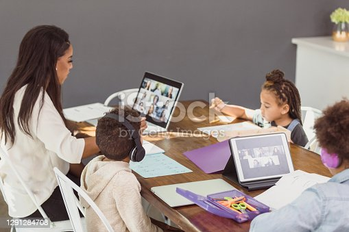 Three children learn from home during the coronavirus pandemic. Their mom is sitting at the table with them, participating in a virtual meeting with colleagues.