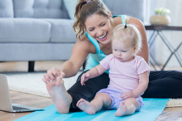 Mom works out with baby girl stock photo