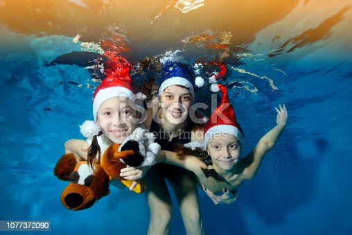 Girl underwater in a white mask posing on the blue background. Portrait. Horizontal orientation. Shooting under water.