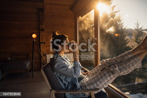Photo of a young woman enjoying some alone time during her winter vacation in the mountains