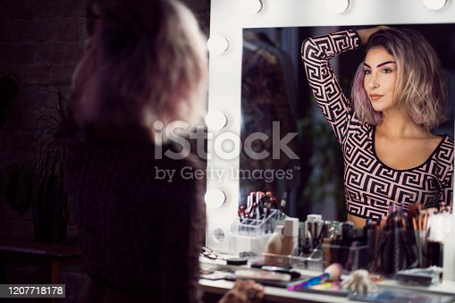 Young, confident woman looking at the mirror after putting a makeup.