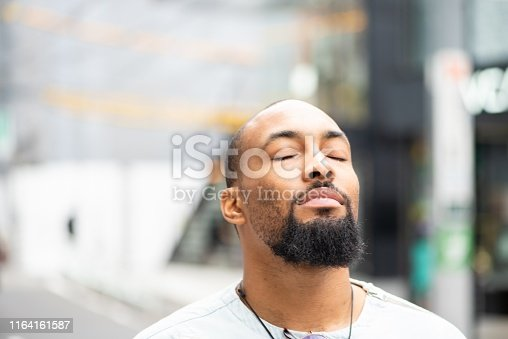 A handsome man standing outside with his eyes closed, enjoying a moment of peace.